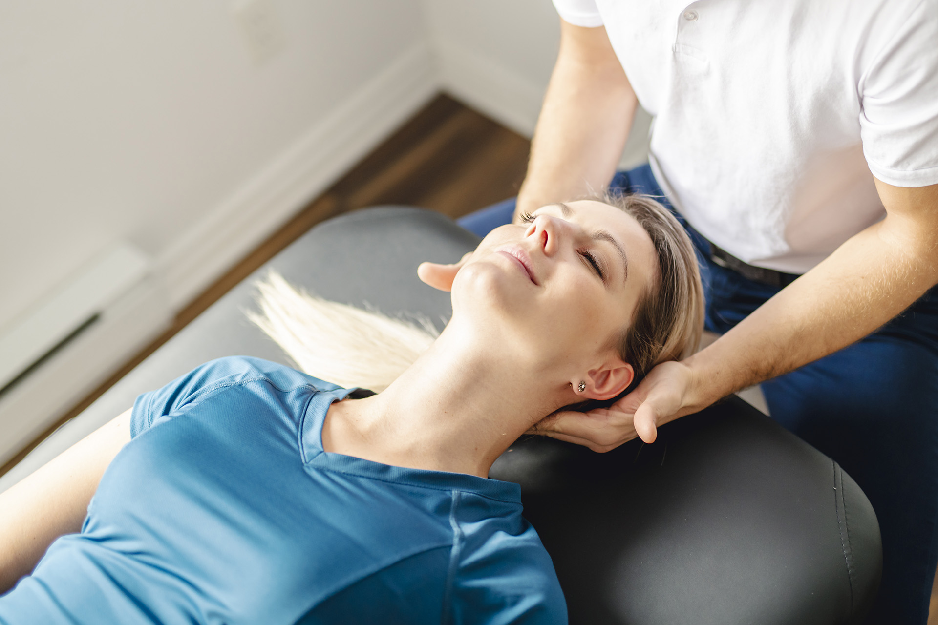 image: woman laying on back while a male physical therapist adjusts her neck