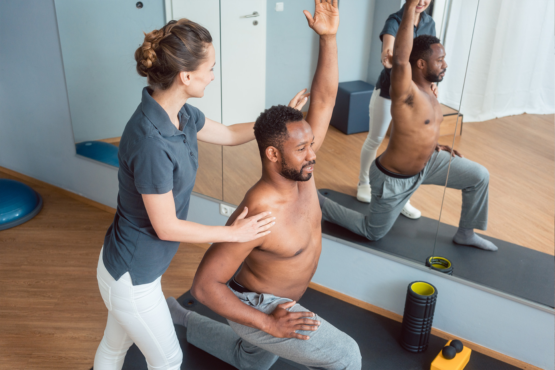 Image: man being helped to stretch by a woman physical therapist