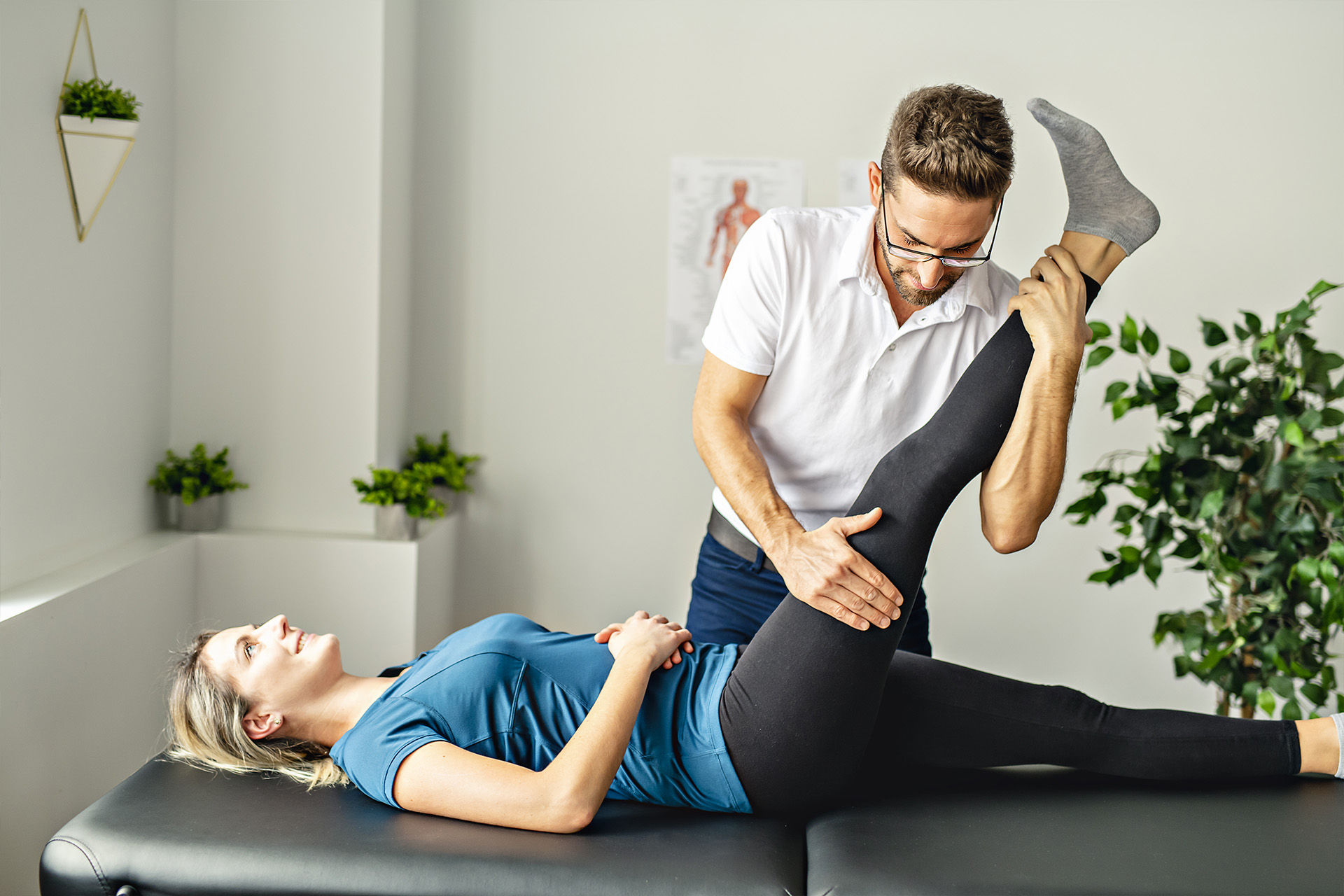 Image: male physical therapist rotates and stretches female patient's leg